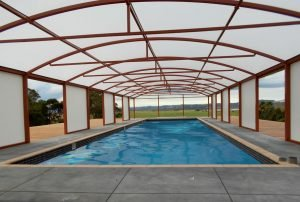 Free standing arched canopy covering a pool by Fresco Shades